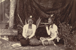 A couple of Burmese young ladies, one of whom is engaged in making 'cheroots', an occupation which fills up a good deal of their time, the demand for these articles in Burmah being very great